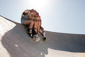 Women skaters using mobile phone