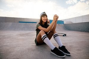 Cool female skateboarder relaxing