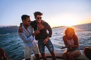Friends enjoying in a sunset boat