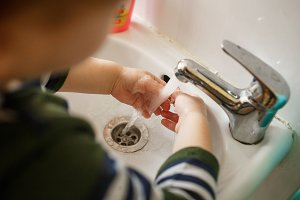 Child washing hands in a white basin with soap