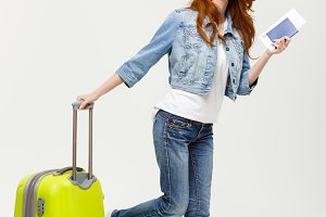 Travel and Lifestyle Concept: young woman with suitcase ready for summer travel isolated on white