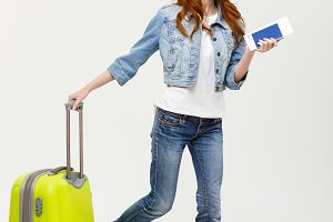 Travel Concept: Young Caucasian Woman traveler with suitcase isolated on white background.