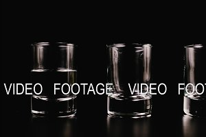 Vodka fills a glass on a black background. Stop motion, animation