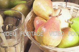 Slow motion pears in a basket and a glass of juice