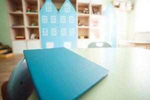 Diploma of educator on kindergarten interior background Education and graduation concept