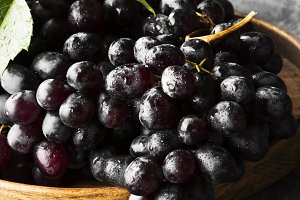 Dark grapes in wooden bowl