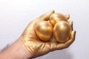Golden egg on golden hand
