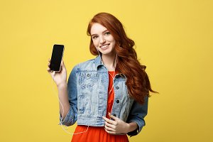 Portrait of a happy woman in earphones listening to music while standing and showing blank screen mobile phone isolated over yellow background