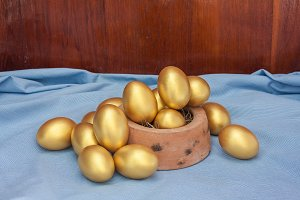 Stack of golden easter egg in bowl