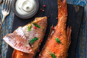 Delicious smoked fish ocean perch on wooden background, top view
