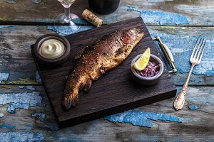 Smoked trout with spices on a stone tray.