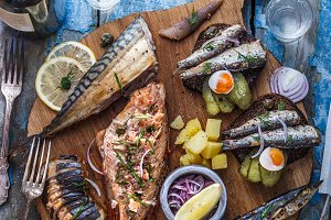 Assorted smoked fish on wooden cutting board, top view