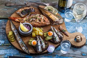 Smoked fish appetizers with mackerel, sturgeon, perch on woden cutting board