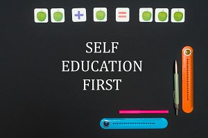 Black art table with stationery supplies with text self education first on blackboard
