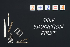 School supplies placed on black background with text self education first