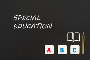 abc letters and chipboard miniature on blackboard with text special education