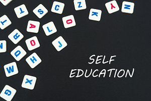 english colored square letters scattered on black background with text keep self education