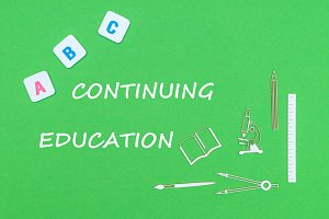 text continuing education, from above wooden minitures school supplies and abc letters on green background