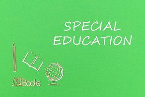 text special education, school supplies wooden miniatures on green background