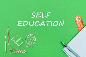 text self education, school supplies wooden miniatures, notebook on green background