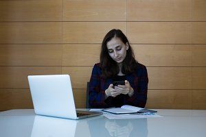 Young woman typing on her phone