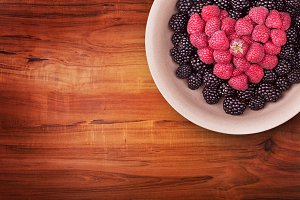 Plate with berries on the wooden table