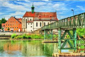 St. Oswald Church with Eiserner Steg bridge across the Danube River in Regensburg, Germany