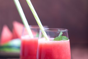 Fresh watermelon cocktail in two glasses on a dark wooden rustic background