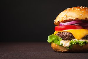 Close-up of delicious fresh home made burger with lettuce, cheese, onion and tomato on a dark background with copy space