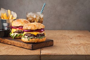 Close-up of delicious fresh home made burger with lettuce, cheese, onion and tomato on a rustic wooden plank on a dark background. Also fries and Cola with ice with copy space