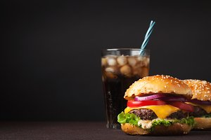 Close-up of delicious fresh home made burger with lettuce, cheese, onion, tomato and cola with ice on a dark background with copy space