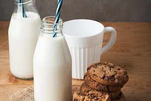 Two bottles of milk and chocolate chip cookies on dark background with copy space