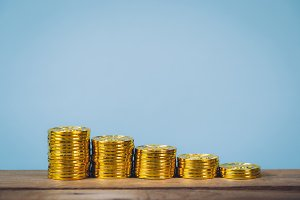 Gold coins stack over blue pastel background with copy space. Business growing and Money saving concept