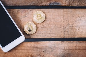 Two coins of Crypto currency Bitcoin with smart phone with copy space over wooden background. Cryptocurrency and future of digital financial banking trade