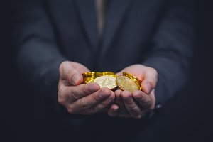 Close-up of businessman's hands full of bitcoin sign of coins - cryptocurrency financial trade wealth and business investment and blockchain technology