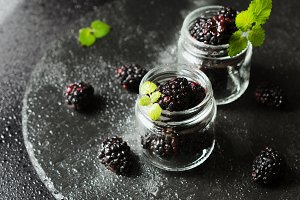 ripe blackberries in a glass jar, breakfast on a rustic table, selective focus