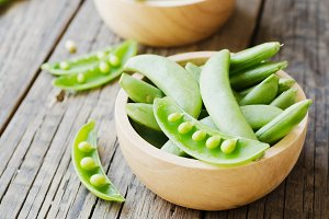 green peas in a wooden bowl on a rustic table, selective focus