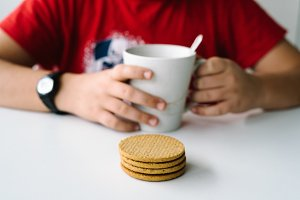 Close up of boy having a breakfast with biscuits, focus on biscu
