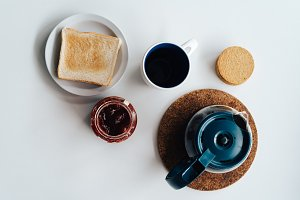 Lay flat of breakfast with coffee, biscuits and toast with jam