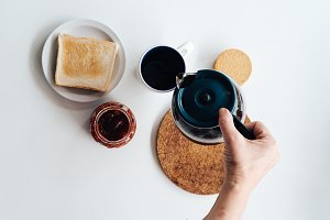 Lay flat of breakfast with woman hand serving coffee, biscuits a