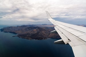 Airplane wing during flight with ground and sea on background