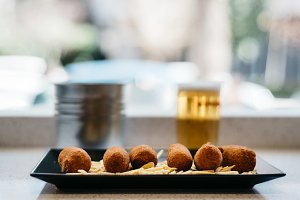 Close up of croquettes with potatoes with beer on background