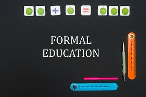 Black art table with stationery supplies with text formal education on blackboard