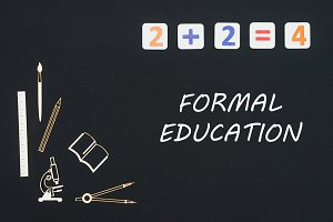 School supplies placed on black background with text formal education