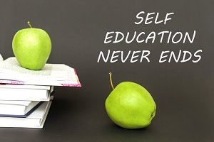 text self education never ends, two green apples, open books with concept