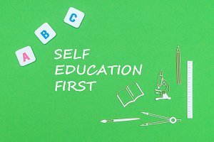 text self education first, from above wooden minitures school supplies and abc letters on green background