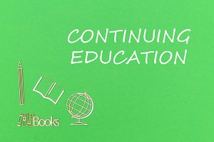text continuing education, school supplies wooden miniatures on green background