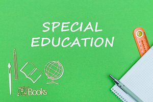 text special education, school supplies wooden miniatures, notebook on green background