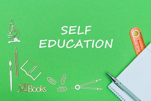 text self education, school supplies wooden miniatures, notebook with ruler, pen on green backboard
