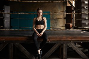 Serious 18 year old girl with braids sitting on edge of boxing ring, ready for training, waiting for her coach. Portrait of focused sporty woman wearing stylish sports bra, leggings and running shoes